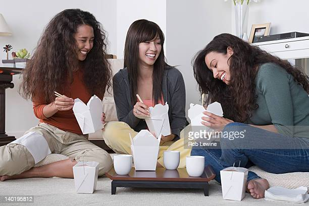 USA, California, Los Angeles, Three female friends eating take out food at home