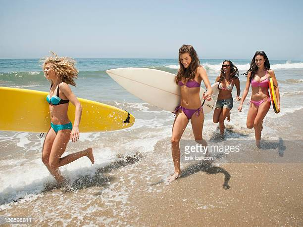 usa, california, malibu, group of young attractive women running into water with surfboards - マリブ ストックフォトと画像