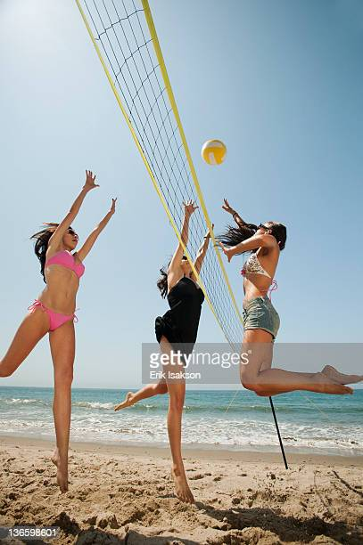 USA, California, Malibu, Three attractive young women playing beach volleyball