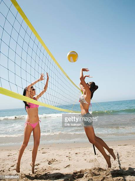 USA, California, Malibu, Two attractive young women playing beach volleyball
