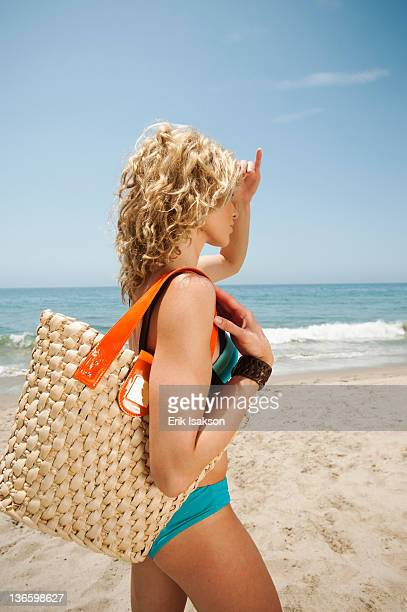 USA, California, Malibu, young attractive woman carrying straw bag on sandy beach