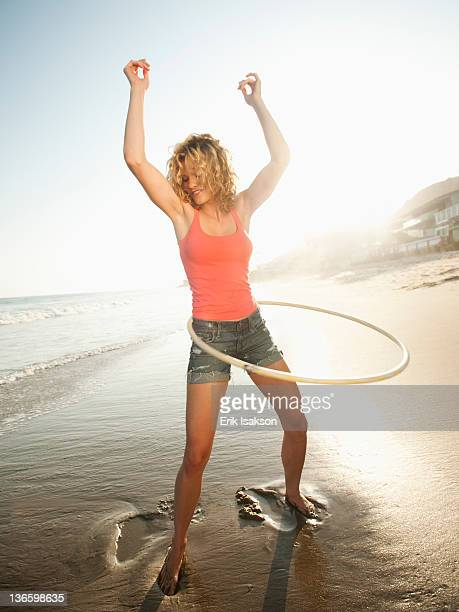 USA, California, Malibu, Young attractive woman exercising with hoola hoop