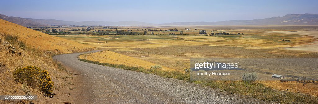 USA, California, near Eagleville, gravel road and Surprise Valley in background : Foto stock