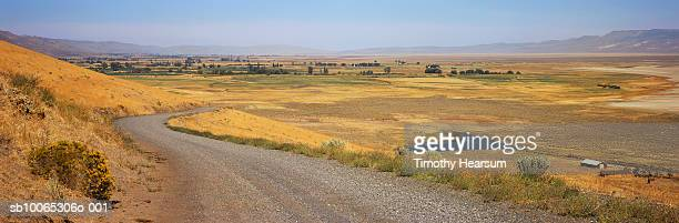 usa, california, near eagleville, gravel road and surprise valley in background - timothy hearsum ストックフォトと画像