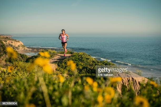 usa, california, newport beach, woman running along cliff - newport ca stock pictures, royalty-free photos & images
