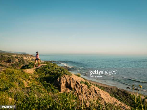 usa, california, newport beach, woman running along cliff - newport beach stock pictures, royalty-free photos & images