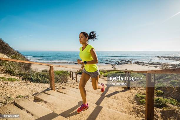 usa, california, newport beach, woman running up stairs - california strong stock photos and pictures