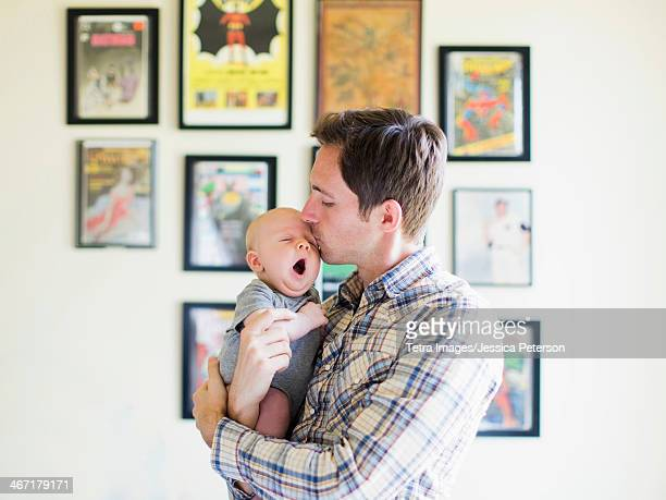 usa, california, orange county, father kissing baby son (2-5 months) - leanintogether stock pictures, royalty-free photos & images