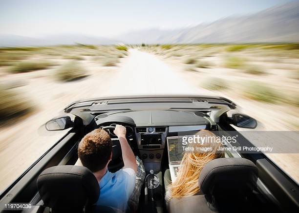 USA, California, Palm Springs, Coachella Valley, San Gorgonio Pass, Couple driving through desert in convertible car