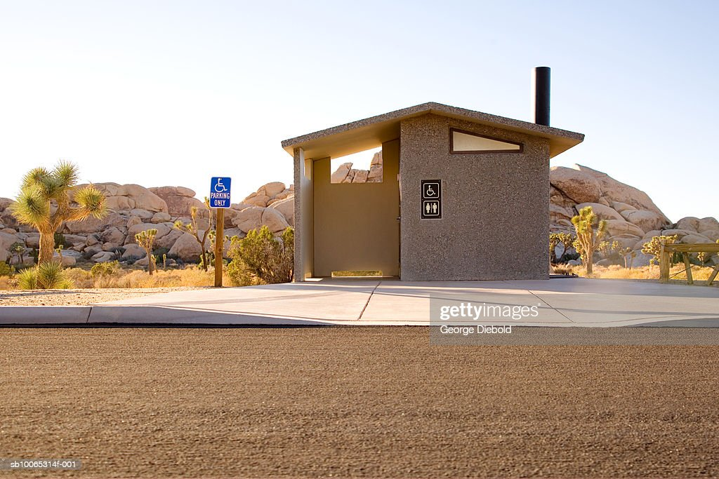 USA, California, Palm Springs, roadside public toilet building, Joshua trees and rock formation in background : Foto stock