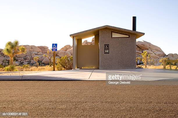 USA, California, Palm Springs, roadside public toilet building, Joshua trees and rock formation in background