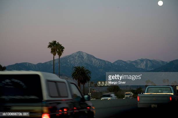 USA, California, Palm Springs, Traffic on highway at dusk, mountains in background