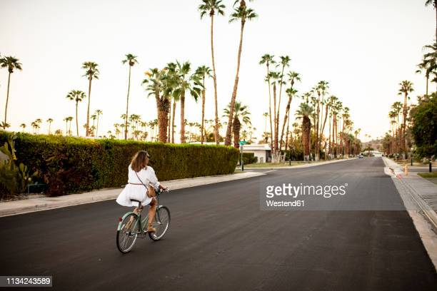 usa, california, palm springs, woman riding bicycle on the street - palm springs stock-fotos und bilder