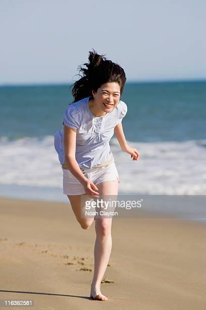 usa, california, point reyes, young woman running on beach - pantalón corto fotografías e imágenes de stock