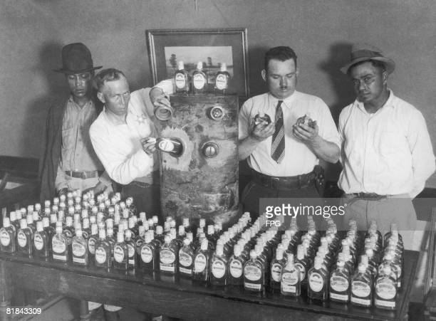 California prohibition agents with a vehicle fuel tank and the 250 bottles of tequila which were hidden in it and smuggled into the US from Mexico...