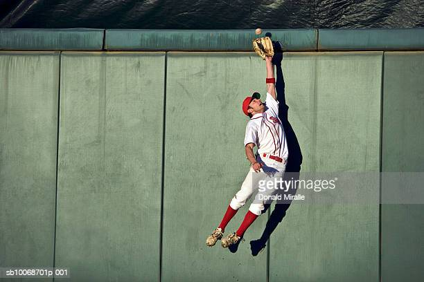 usa, california, san bernardino, baseball player making leaping catch at wall - baseball sport stock pictures, royalty-free photos & images