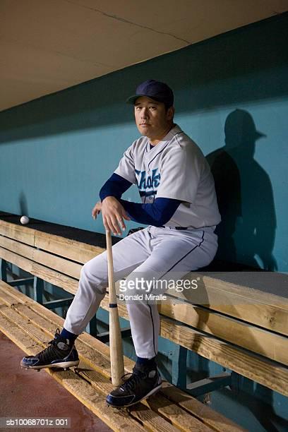 USA, California, San Bernardino, baseball player sitting in dugout, portrait
