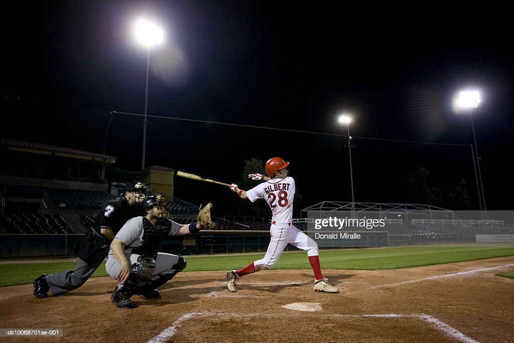 USA, California, San Bernardino, baseball players with batter swinging : Stock Photo