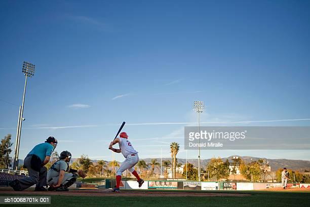usa, california, san bernardino, baseball players with batter swinging - baseball player stock pictures, royalty-free photos & images