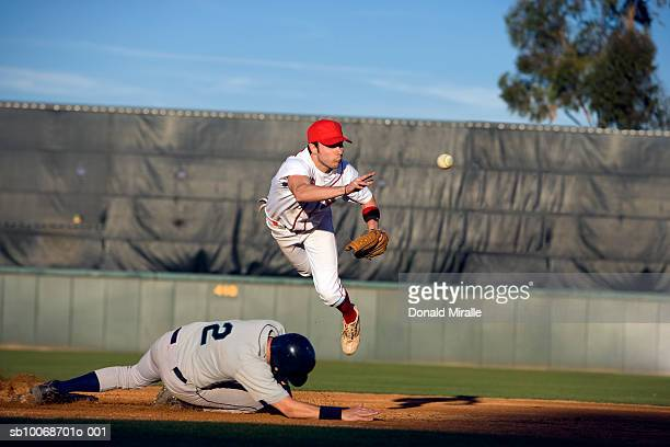usa, california, san bernardino, baseball runner sliding for base and baseman leaping for catch - catching stock pictures, royalty-free photos & images