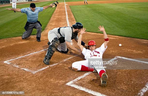 USA, California, San Bernardino, baseball runner sliding safely into home base