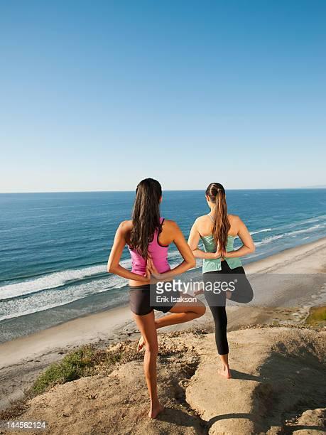 USA, California, San Diego, Two women practicing yoga on beach