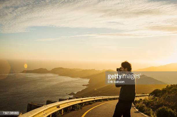 USA, California, San Francisco, California, Silhouette of man photographing coastline at sunset