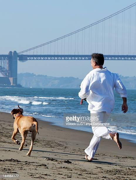 USA, California, San Francisco, Man and dog running along seashore