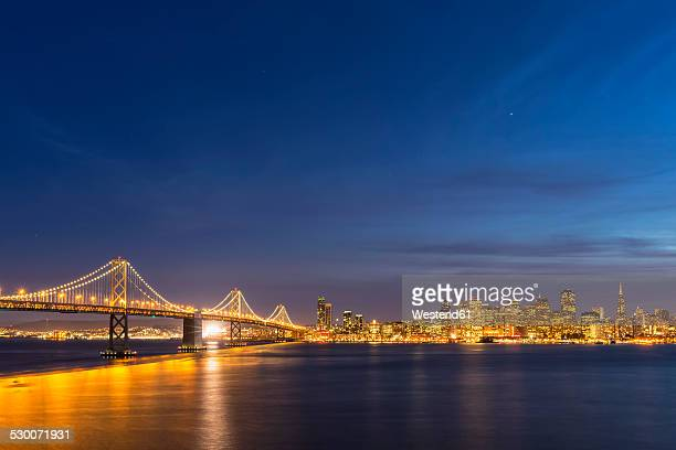 usa, california, san francisco, skyline and oakland bay bridge in the evening - bay bridge stock pictures, royalty-free photos & images