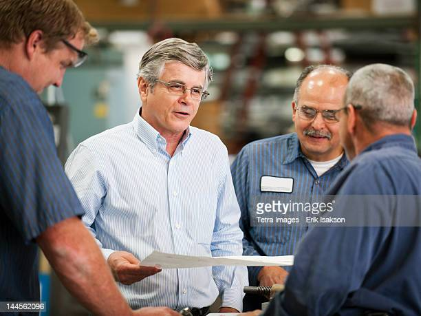 USA, California, Santa Ana, Businessman and workers talking in factory