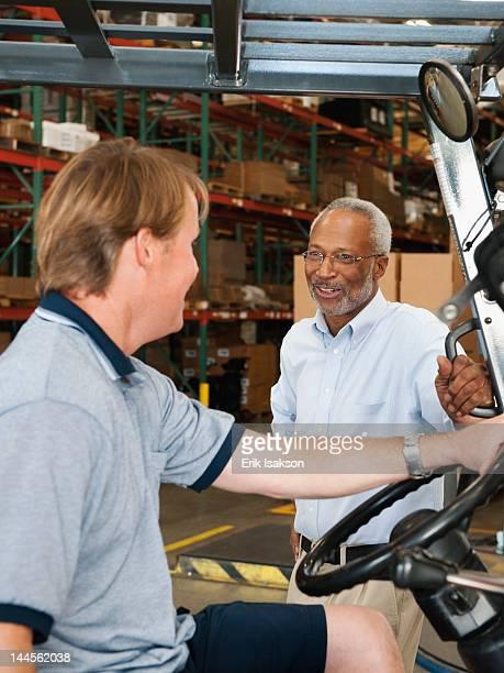 usa, california, santa ana, businessman talking to forklift driver in warehouse - santa ana california stock pictures, royalty-free photos & images