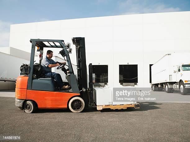 USA, California, Santa Ana, Man driving forklift