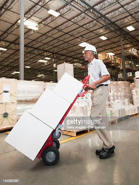 usa, california, santa ana, man pushing hand truck in warehouse - printed media stock pictures, royalty-free photos & images