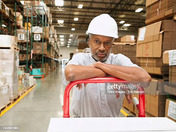 usa, california, santa ana, portrait of man pushing hand truck in warehouse - santa ana california stock pictures, royalty-free photos & images