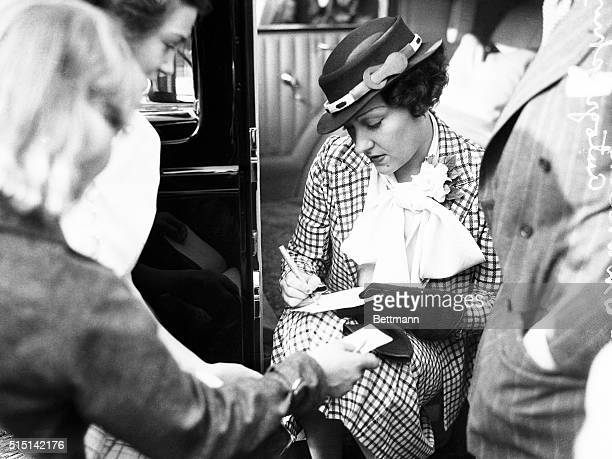 """California: """"Signed--Gloria."""" Gloria Swanson, famous motion picture star, adds her signature to the collections of autograph hounds on her arrival in..."""