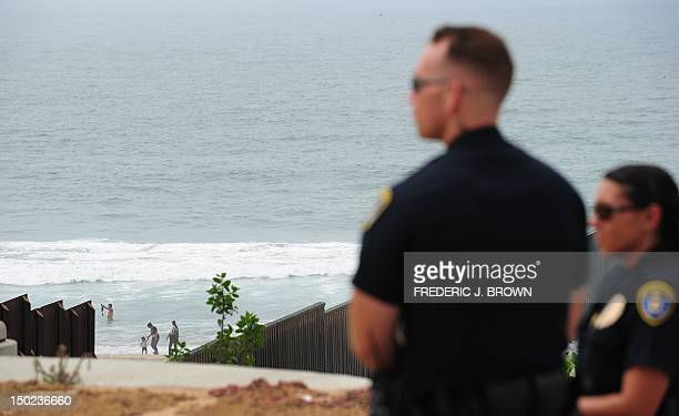 California State Parks guards on duty as adults and children play at the beach on the Tijuanaside of the Border Field State Park fence which...