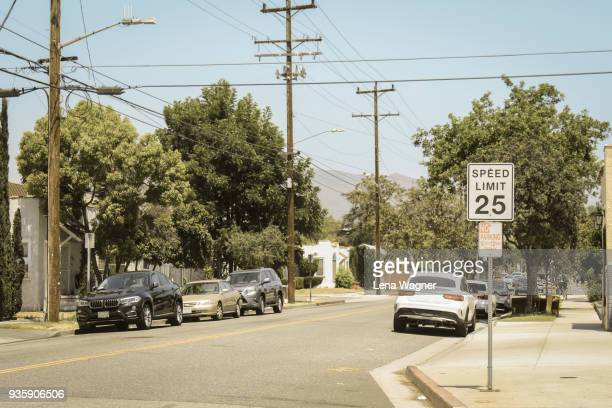 california street with parked cars and trees - speed limit sign stock photos and pictures