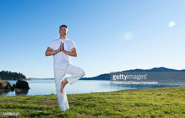 usa, california, tiburon, man practicing yoga at lakeshore - endast medelålders män bildbanksfoton och bilder