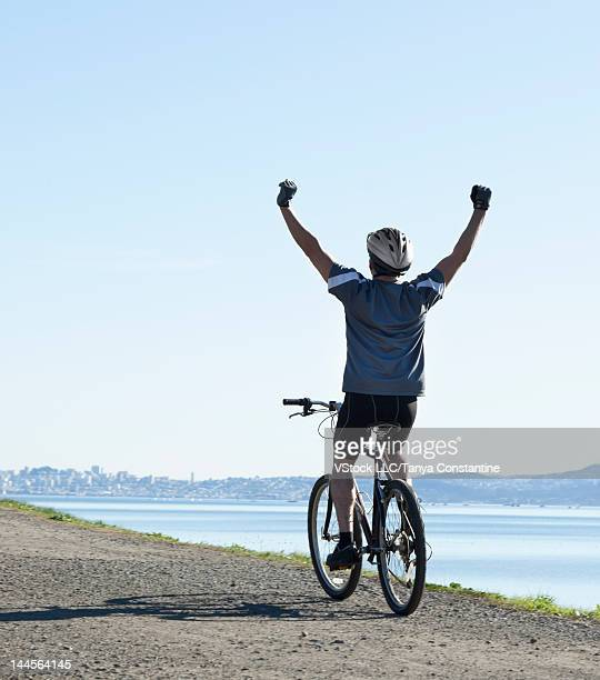 USA, California, Tiburon, Man riding bike along lakeshore with arms up