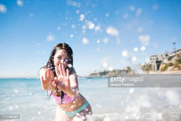 USA, California, Woman playing in water on Laguna Beach