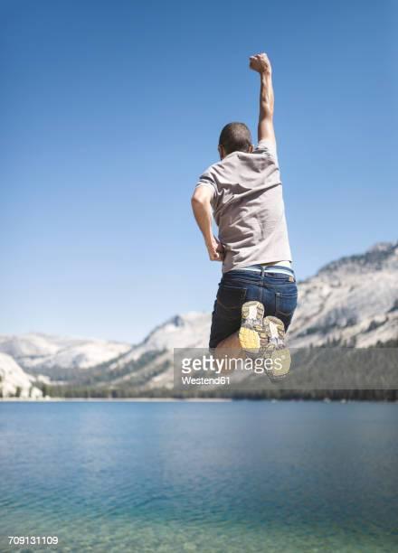 USA, California, Yosemite National Park, back view of man jumping in the air at mountain lake