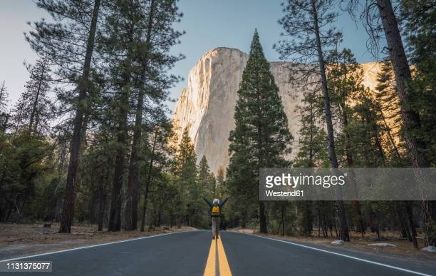 usa, california, yosemite national park, man with raised arms on road with el capitan in background - el capitan yosemite national park stock pictures, royalty-free photos & images