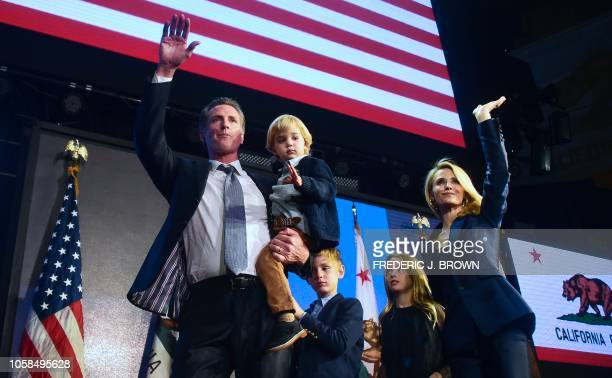 TOPSHOT California's Democratic gubernatorial candidate Gavin Newsom and his family waves to supporters from stage at his election night watch party...