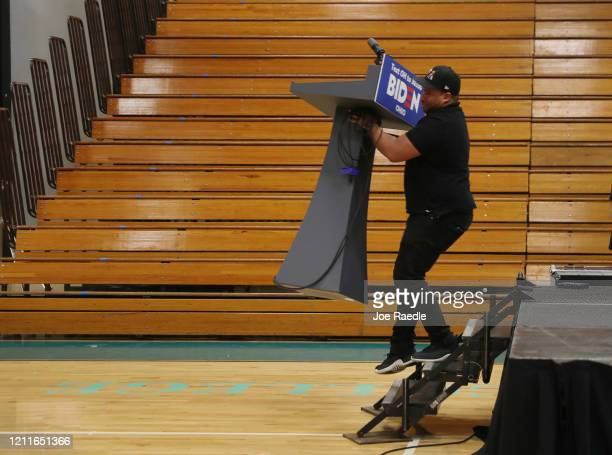 Caliph Mathis carries the podium that had been set up for Democratic presidential candidate former Vice President Joe Biden away after his primary...