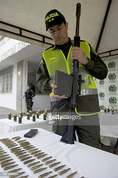 Cali's police commander Alejandro Castaneda handles the magazine of a USmade dualcaliber 50/556 sniper rifle during a press conference on January 30...
