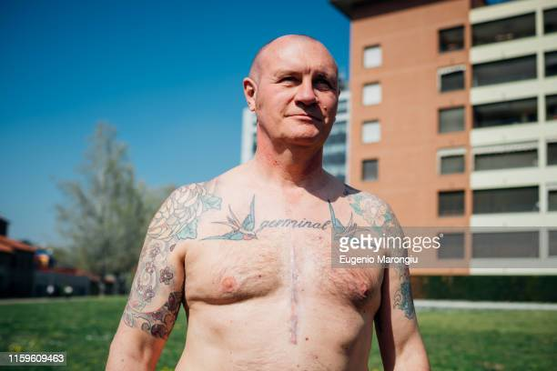 calisthenics in park, bare chested tattooed mature man, portrait - chest barechested bare chested foto e immagini stock