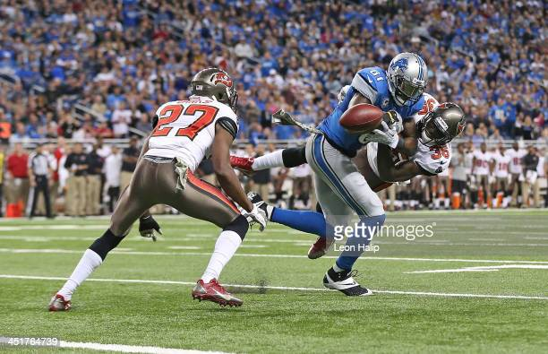 Calivin Johnson of the Detroit Lions makes the catch and the ball is stripped away by Kelcie McGray of the Tampa Bay Buccaneers and intercepted by...