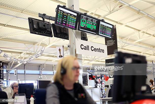A 'Call Centre' sign hangs below a digital information board inside the customer service call center at First Direct bank the online and telephone...