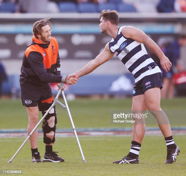 Callan Ward of the Giants is consoled by Tom Hawkins of the Cats after sustaining a leg injury after the team sing the song when winning during the...