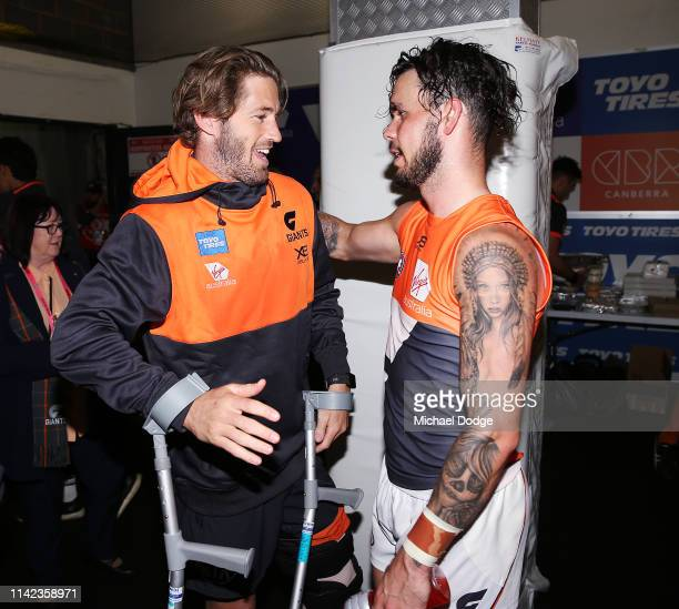 Callan Ward of the Giants is hugged by Zac Williams of the Giants after sustaining a leg injury after the team sing the song when winning during the...